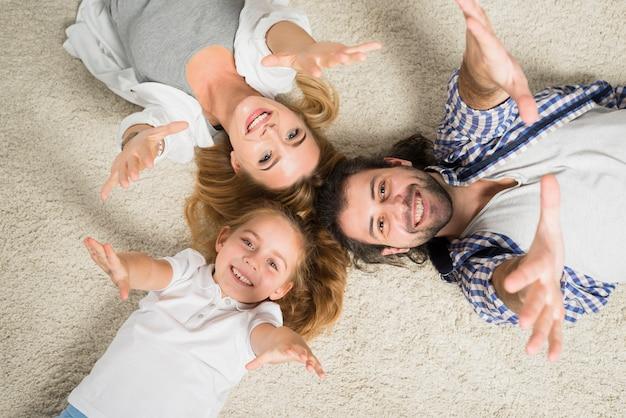 トップビュー家族の肖像画は、カーペットに横たわる