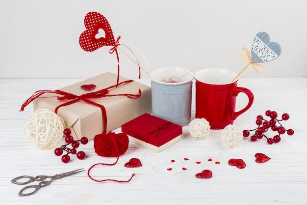 Чашки с сердечками на палочках возле маленьких сердец, ножницы и подарки