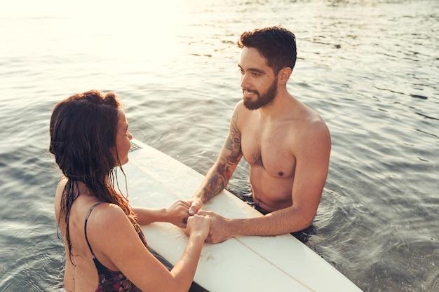 ビーチでサーファーカップル