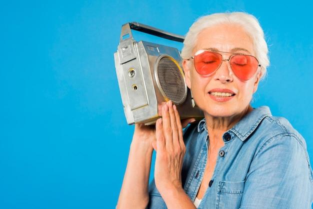 ヴィンテージラジオを持つ現代のシニアの女性