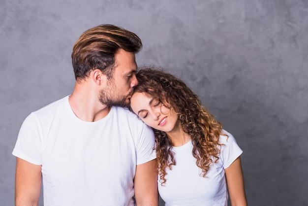 Мужчина целует женщину на лбу