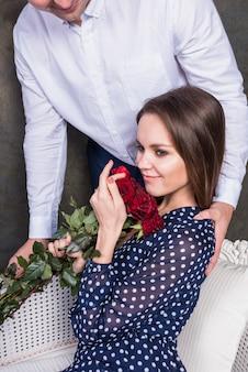 女性にバラの花束を与える男