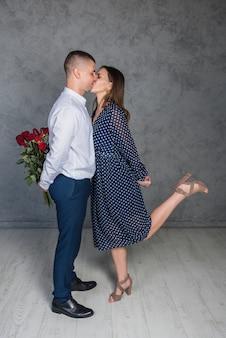 背中の背中にプレゼントをするキスをするカップル