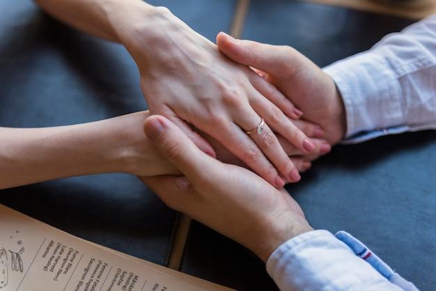 テーブルで男性と女性の手を保持