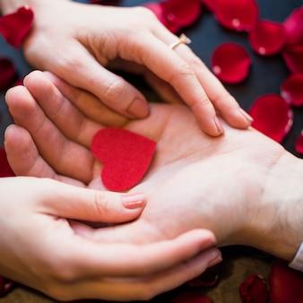 Мужчина представляет красное украшение сердца женщине