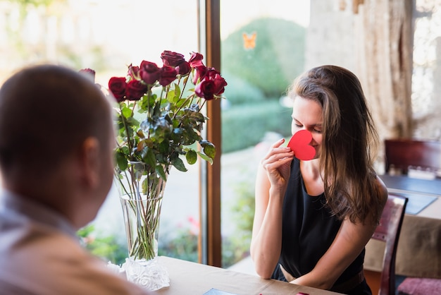 テーブル、装飾心で顔を閉じている男と若い女性