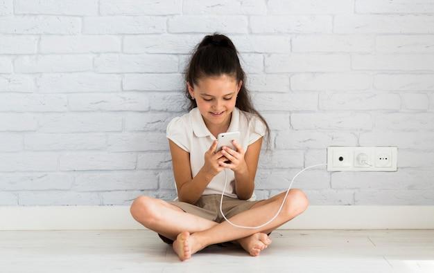 Милая девочка, используя свой смартфон
