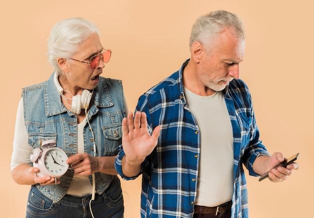 Холодная старшая пара с будильником и смартфоном