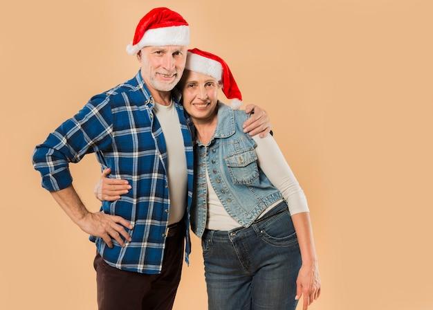クリスマスの帽子を持つシニアのカップル