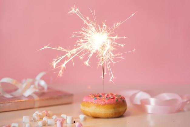 Вид спереди на день рождения пончик с зажженным бенгальским огнем