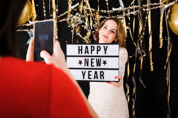 幸せな新年のサインを持っている女の子の写真を撮る