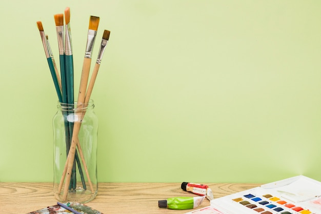 ブラシとカラフルな塗料を使った現代のアーティストコンセプト
