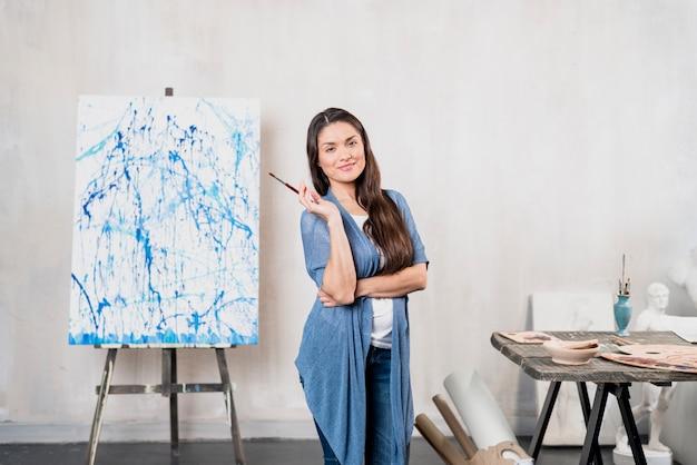 キャンバスの前に女性アーティスト