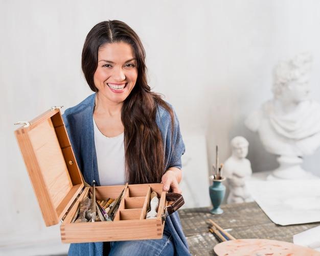 ブラシの木箱を持つ女性アーティスト