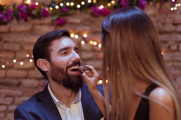 Женщина дарит сладкое улыбающемуся мужчине