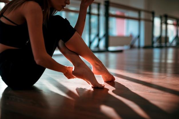 床にポーズを取るプロの女性ダンサー