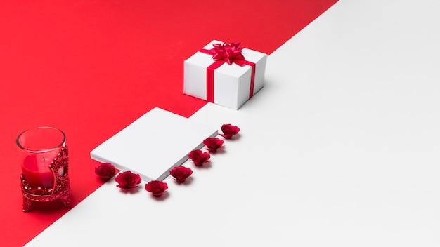 テーブルに小さなバラの芽を持つ空白のメモ帳