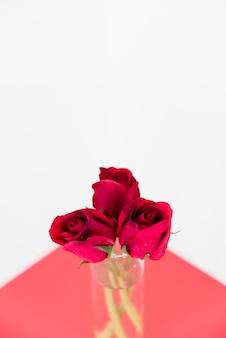 Красные розы в стеклянной вазе на светлом столе