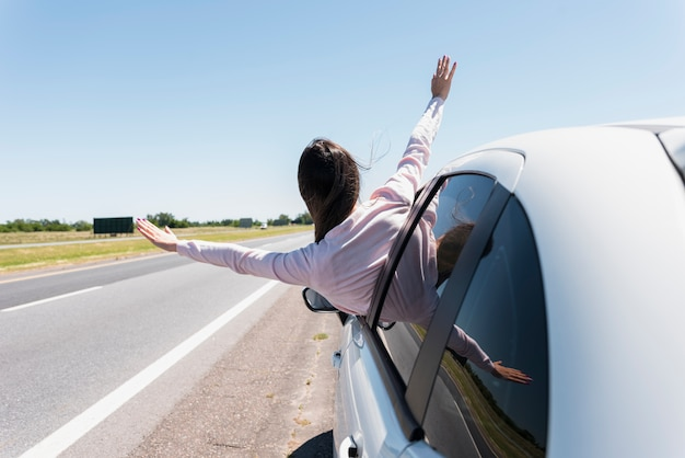 彼女の頭を窓の車の外に置いている少女