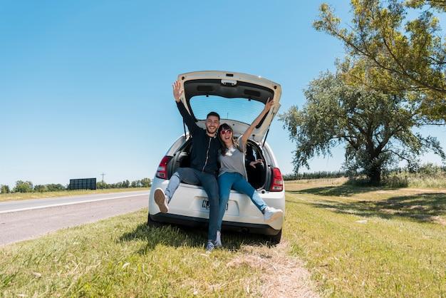 Друзья сидят на багажнике автомобиля, делая знак мира
