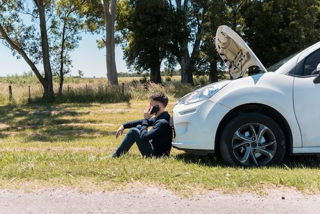 壊れた車の隣に電話する男の子