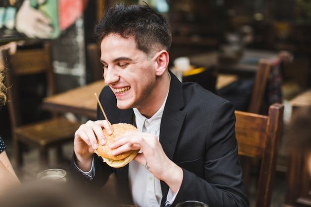 レストランで笑って食べる男