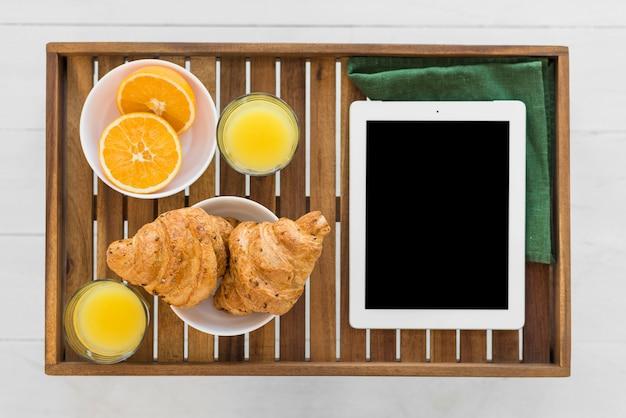 朝食のテーブルの上の食べ物の近くのタブレット