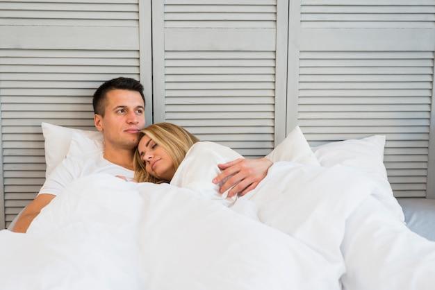 ベッドに横たわっている若い女性を抱きしめるハンサムな抱擁の男
