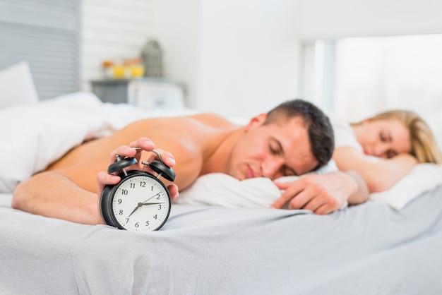 スヌーズの近くのベッドで寝る若いカップル