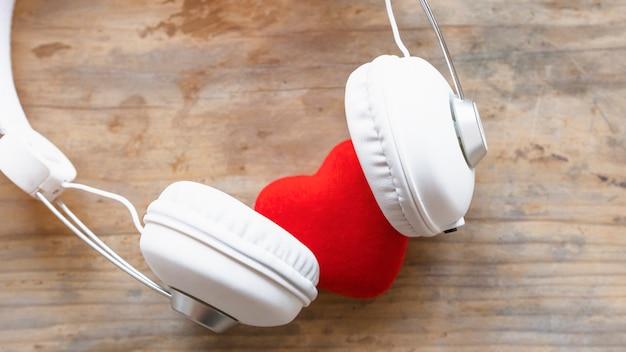 赤い心の木製のテーブルにヘッドフォン