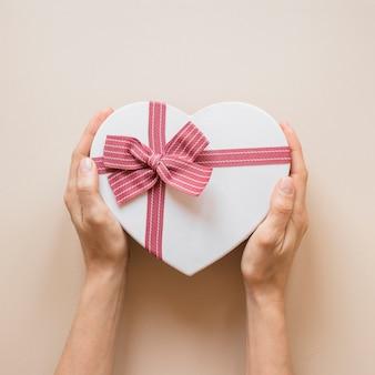 Лицо, занимающее подарочную коробку в форме сердца