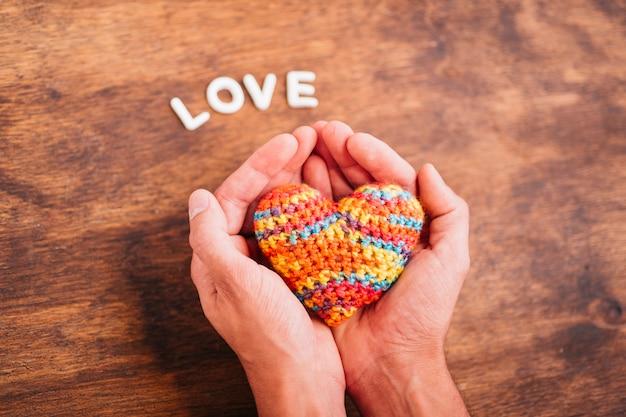 Человек держит игрушечное сердце в руках