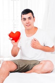 装飾的な心を持って胸に手を持つ男