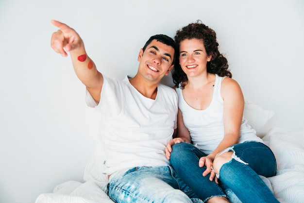 伸ばした手とベッドで寝る女性と若い幸せな男