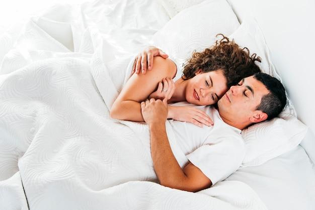 ベッドで羽毛布団の下で眠っている若いカップル