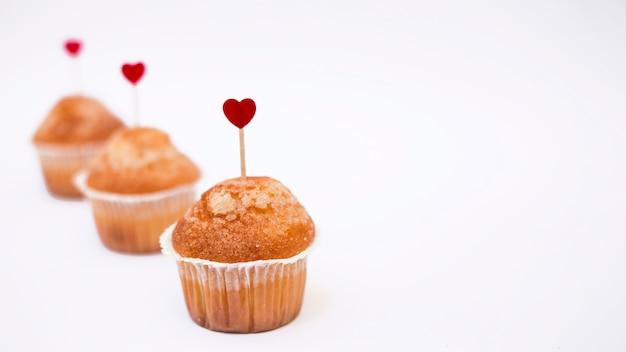 小さな心臓トッパーを持つカップケーキ