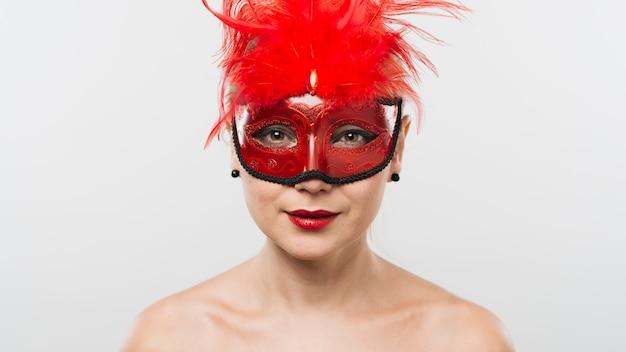 赤い羽毛のマスクの若い女性