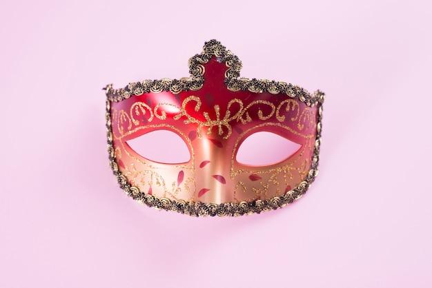 ピンクのテーブルに赤いカーニバルマスク