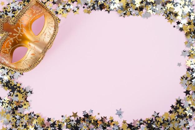 ピンクのテーブルの上に小さなスパンコールのカーニバルマスク