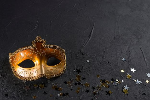 黒いテーブルにスパンコール付きのカーニバルマスク