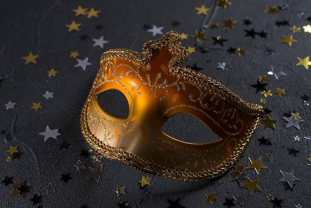 黒いテーブルに小さなスパンコールのカーニバルマスク