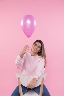 紫色の風船を持つ椅子の若い幸せな女性