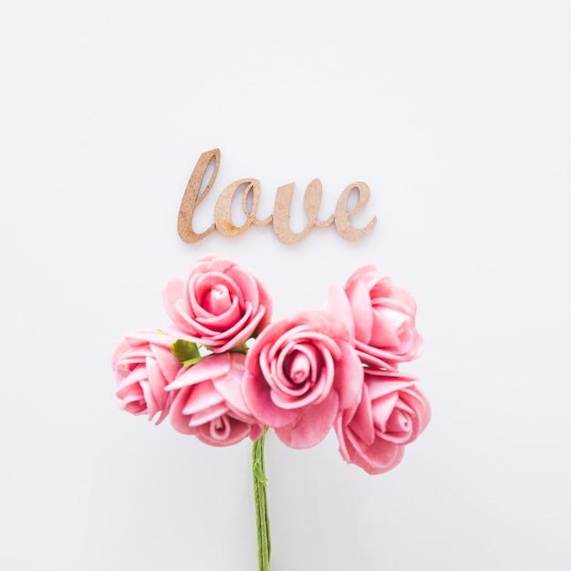 ピンクの偽のバラの近くに書くことを愛する