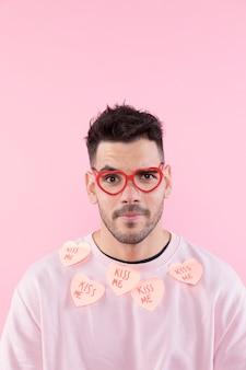 セーターに紙の心を持つ眼鏡の若い男