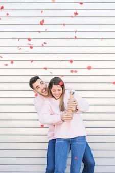 爆笑パーティーポッパーと魅力的な幸せな女性を包む若い笑顔の男
