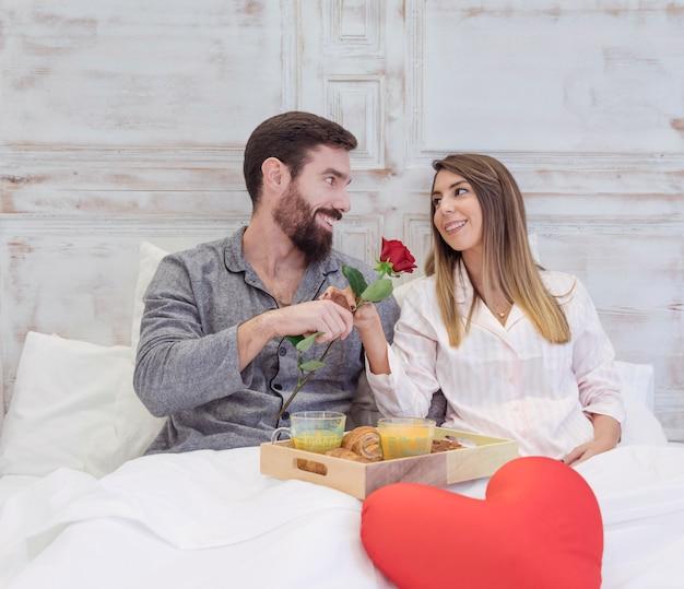男はベッドで女性にバラを与える