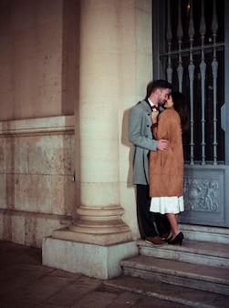 Молодая пара целуется, опираясь на стену здания