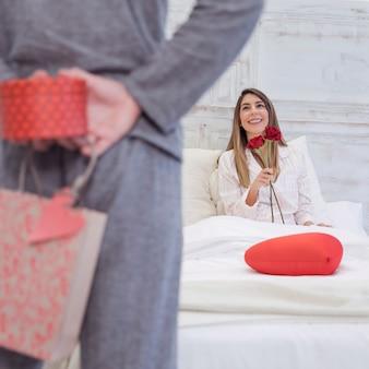 Мужчина держит подарочную коробку для женщины за спиной