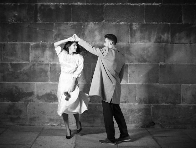夜の通りで踊っている若いカップル