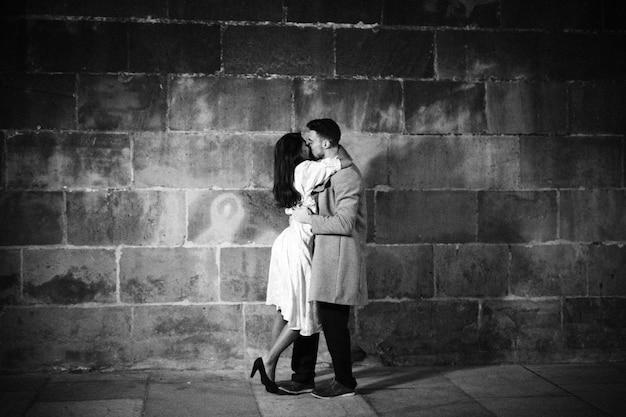 夜の通りにキスしている若いカップル